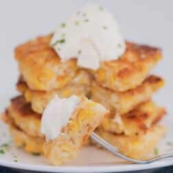 A fork with a piece of corn fritter with a stack of fritters in the background topped with sour cream.