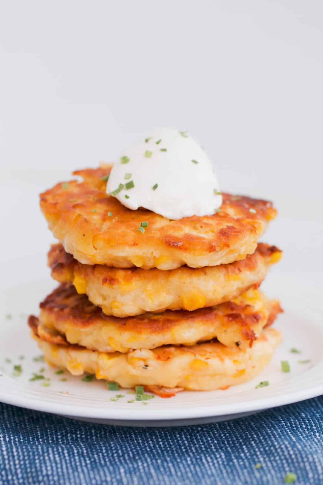 A stack of corn fritters topped with a dollop of sour cream and chopped spring onions.