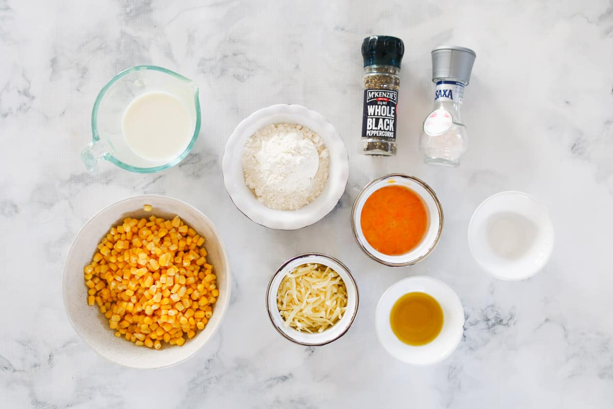 The ingredients needed for corn fritters on a a marble background.