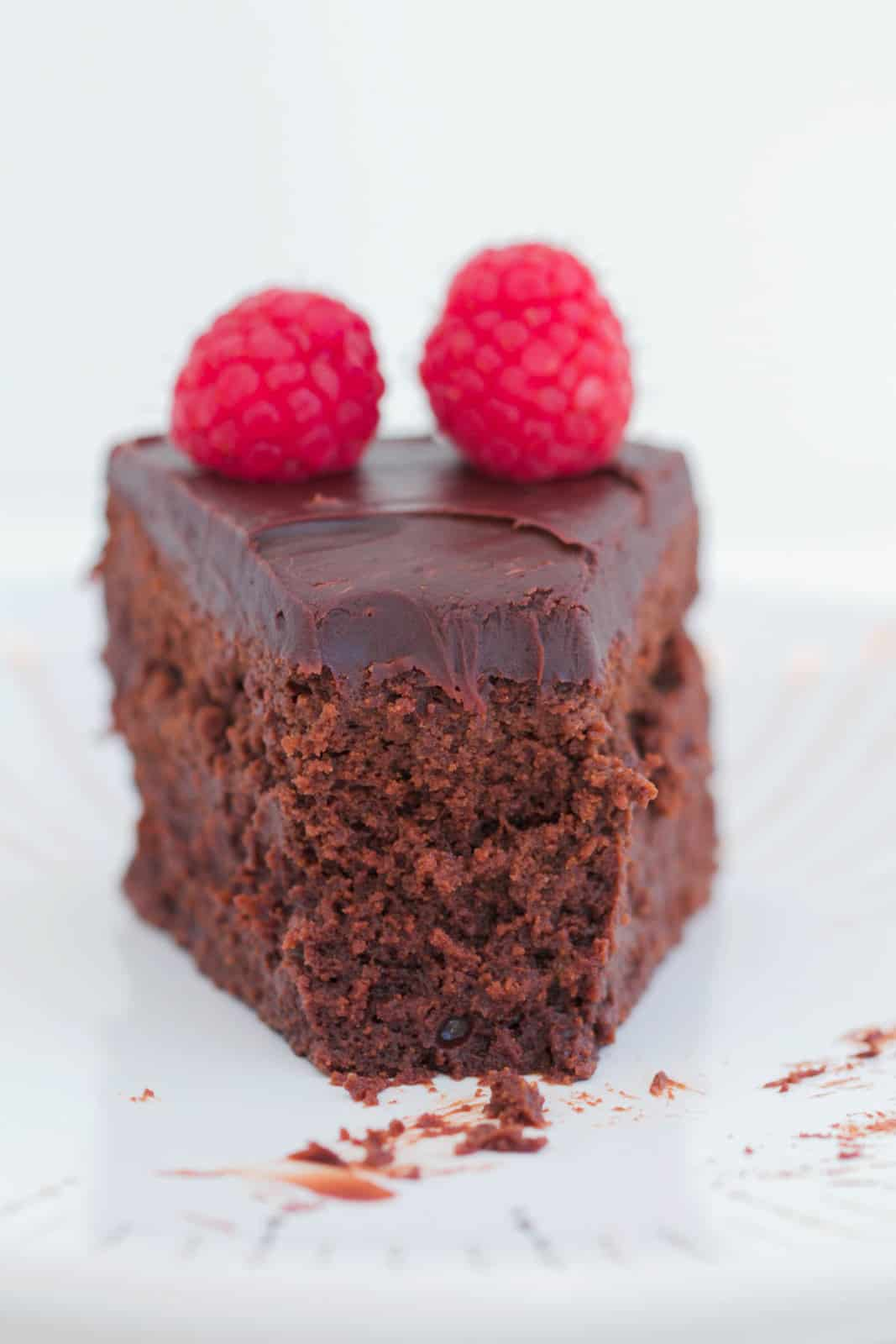 A slice of rich chocolate dessert with a fork mark in it topped with chocolate ganache and fresh raspberries.
