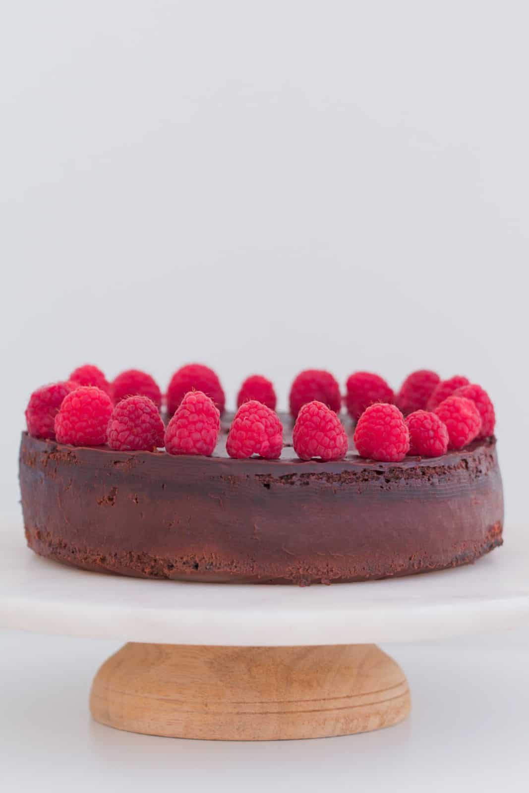 A round dark chocolate mousse cake on a white cake plate decorated with chocolate ganache and raspberries.