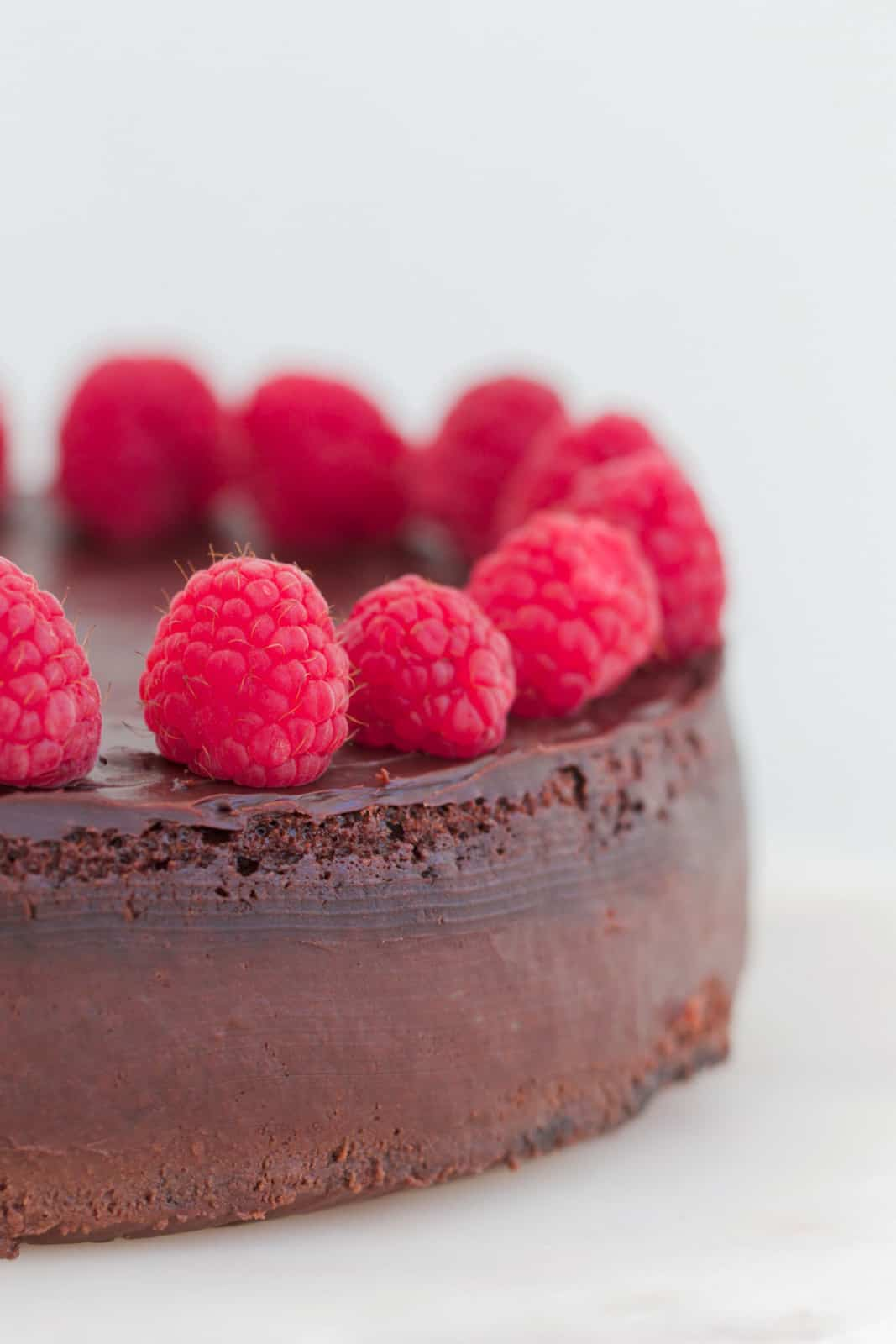 Raspberries and ganache on top of a rich flourless chocolate dessert cake.