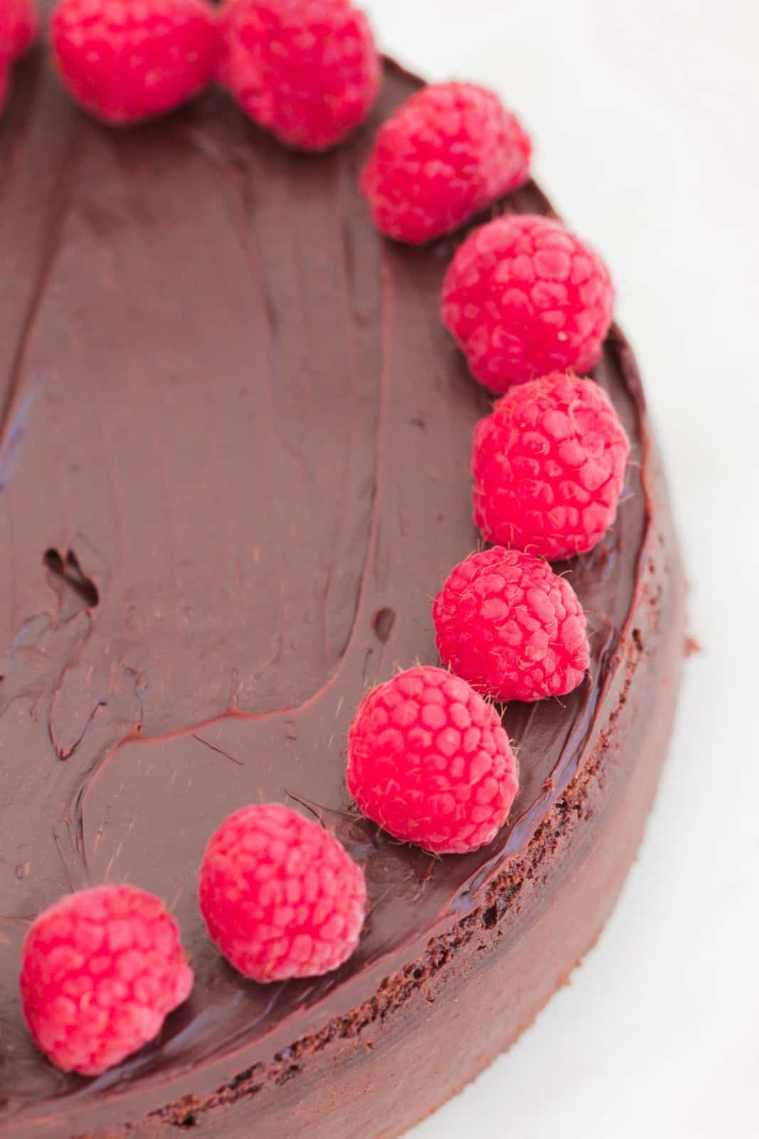 An overhead shot of a chocolate cake covered with ganache and fresh raspberries.