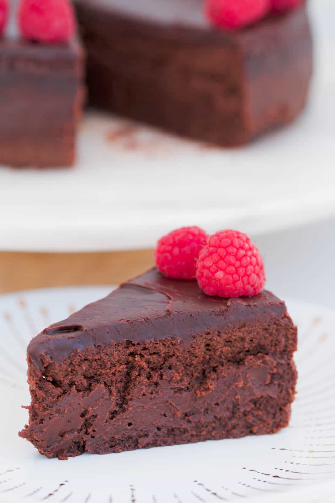 A slice of chocolate mousse cake topped with ganache and raspberries on a white plate.