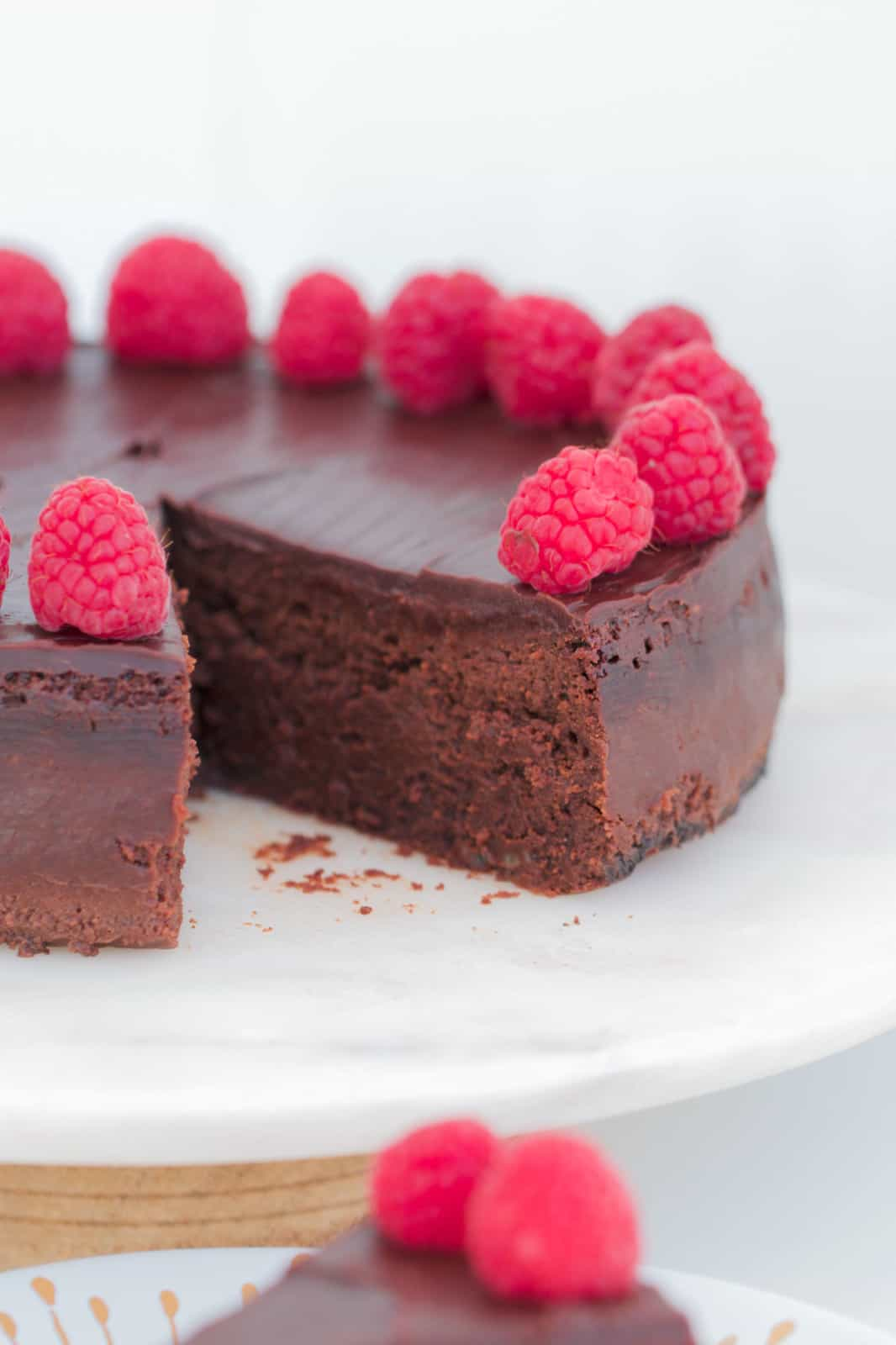 A round chocolate dessert cake decorated with raspberries and ganache. One slice has been one removed showing cake texture.