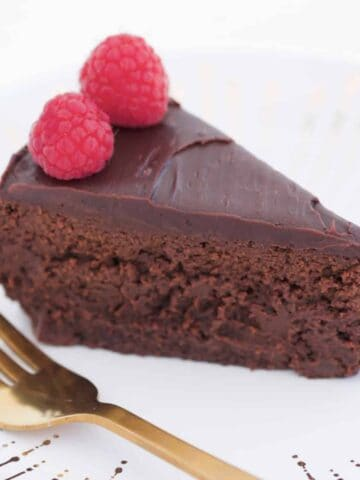 A slice of rich chocolate cake with chocolate ganache and raspberries.