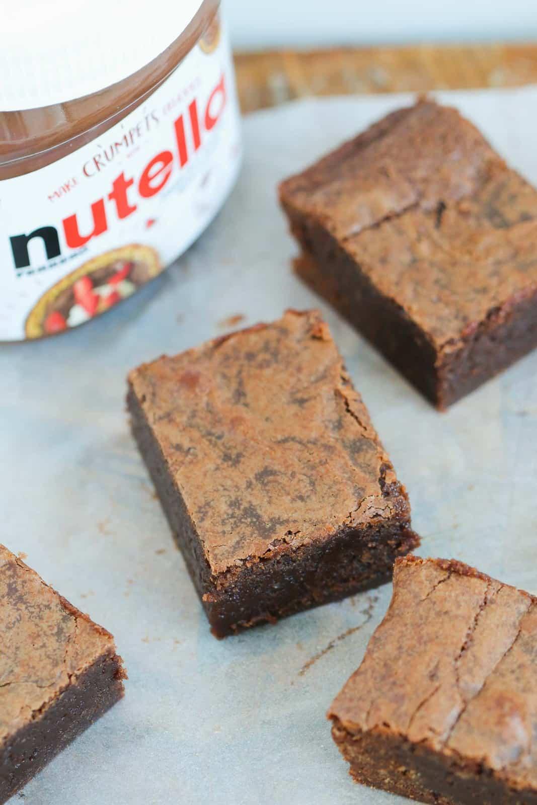 A jar of Nutella chocolate hazelnut spread next to pieces of gooey chocolate brownies.