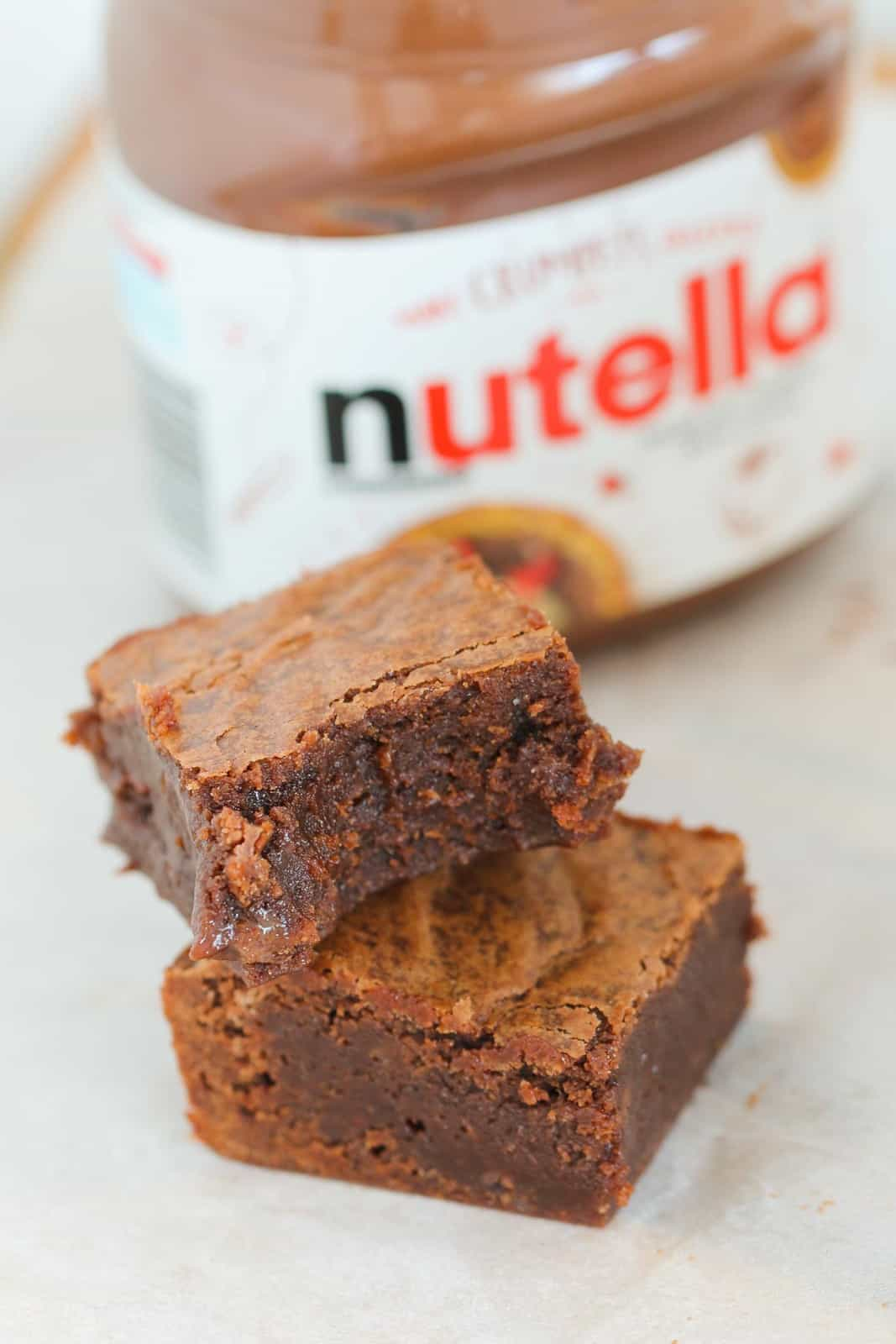 Pieces of chocolate brownie in front of a jar of Nutella Chocolate Hazelnut Spread.
