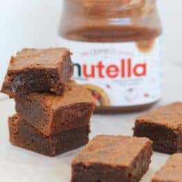 A stack of three chocolate brownies in front of a jar of chocolate hazelnut spread.
