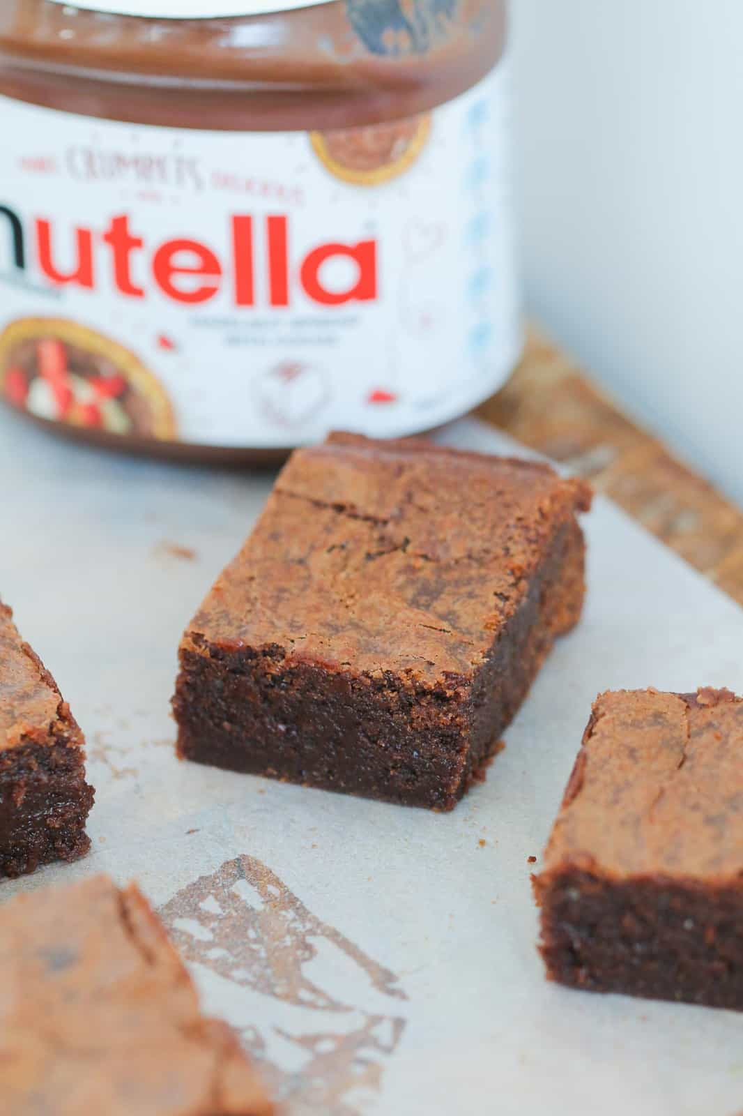 Slices of brownie on a piece of baking paper in front of a jar of Nutella Chocolate Hazelnut Spread