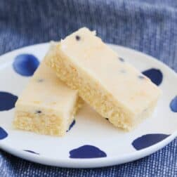 Two pieces of baked slice topped a creamy passionfruit topping on a white and blue plate.