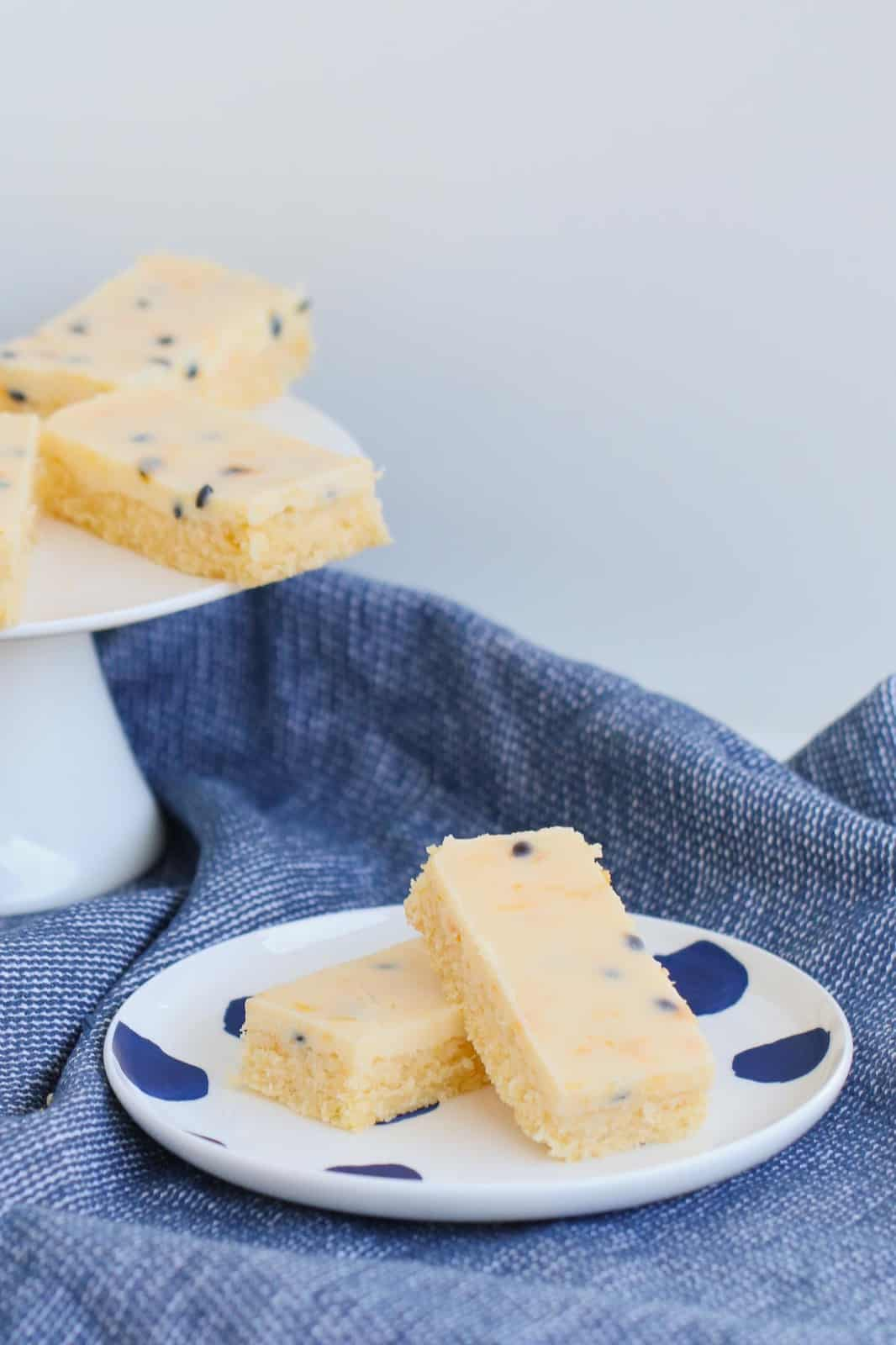 Two pieces of Passionfruit Slice on a white plate with blue dots placed on a blue tea towel.