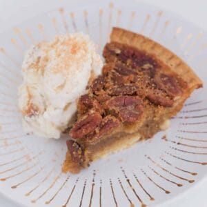 A slice of pecan tart with a scoop of vanilla ice-cream on a white and gold plate.