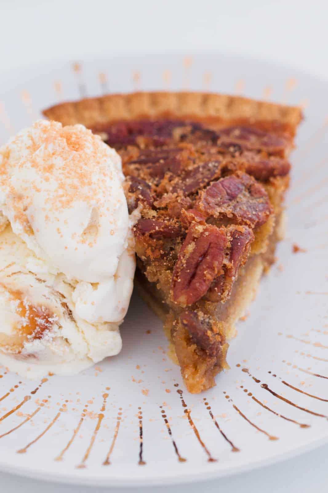 A slice of pecan pie with a scoop of vanilla ice-cream on a white and gold plate.