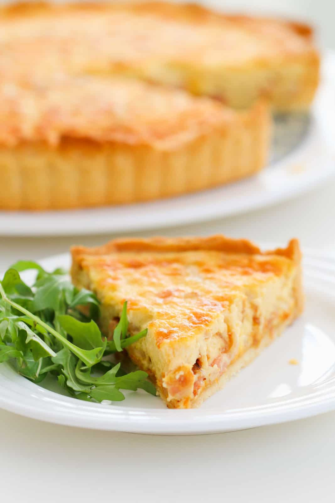 A triangular piece of egg, bacon and cheese quiche on a plate served with rocket leaves