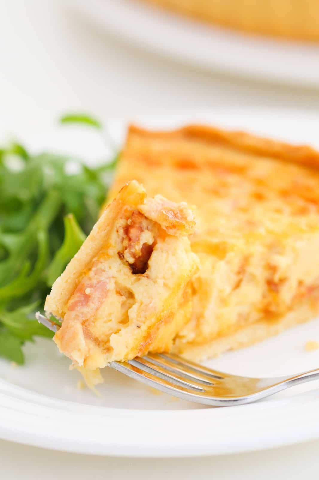 A forkful of egg, bacon and cheese quiche served with rocket leaves