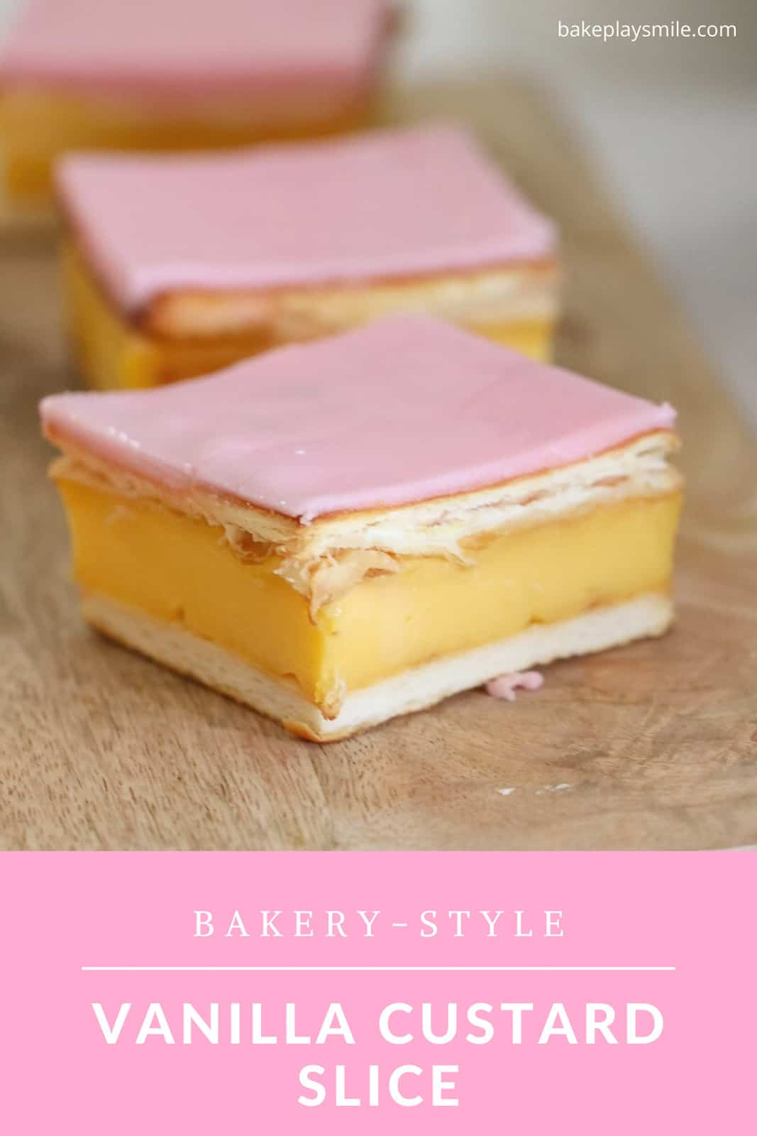 Pieces of custard slice with pastry and pink icing glaze on a wooden board.