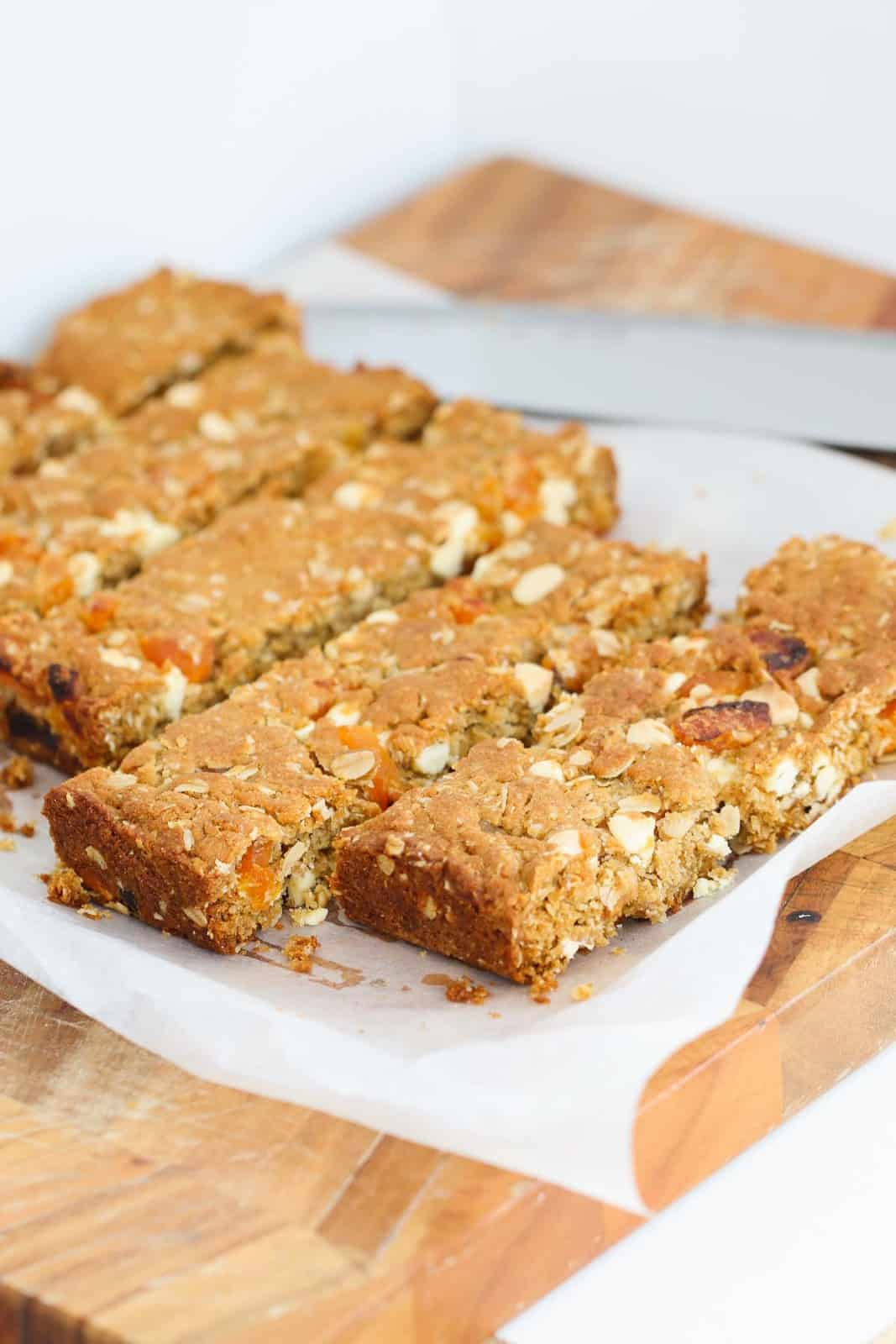 Long apricot oat slices next to each other on a piece of parchment paper on top of a wooden cutting board