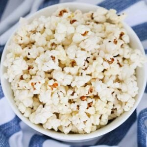 Popped corn kernels on a bowl on a white and blue tea towel.