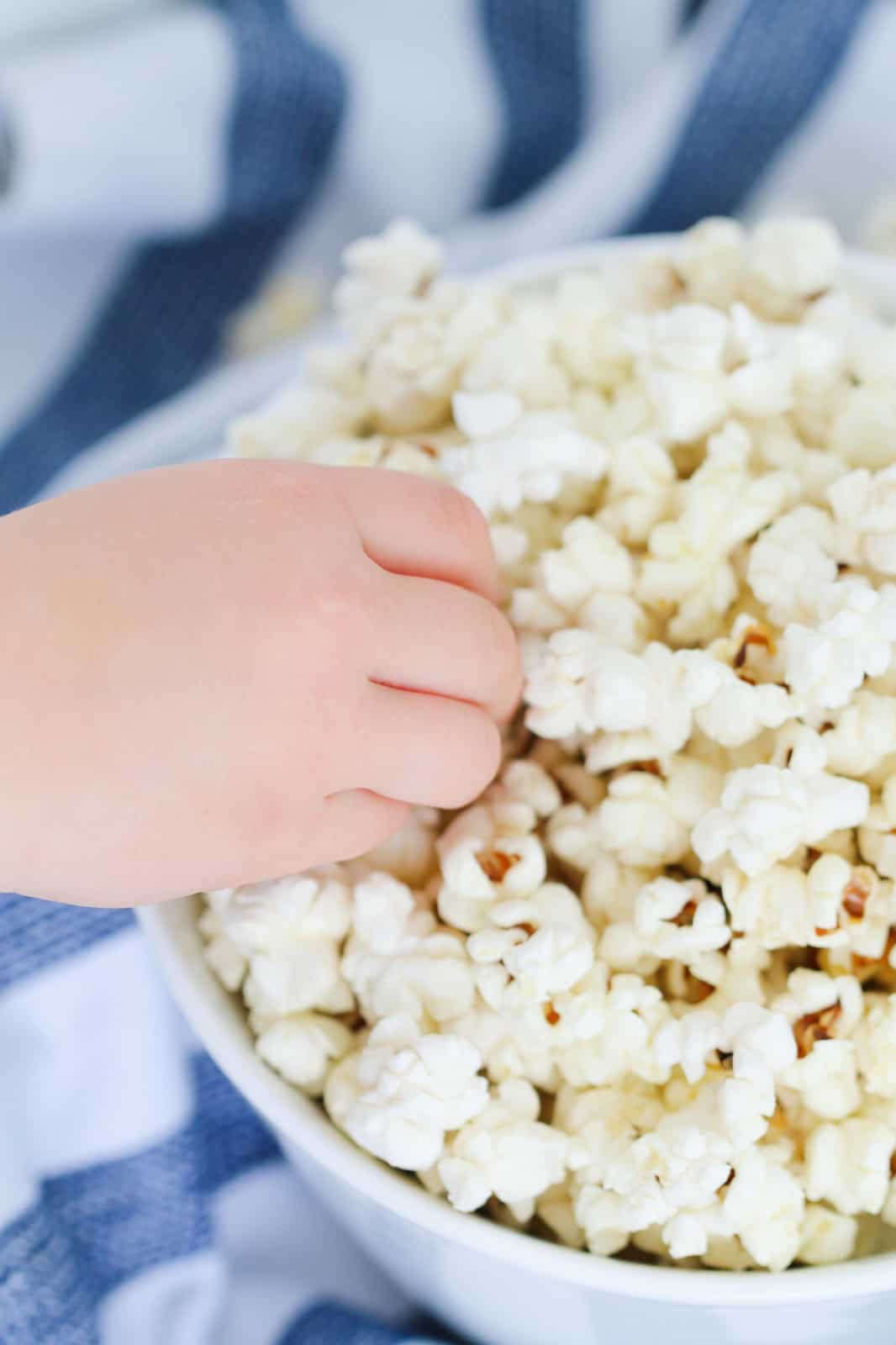 A child's hand reaching into a bowl of popcorn.
