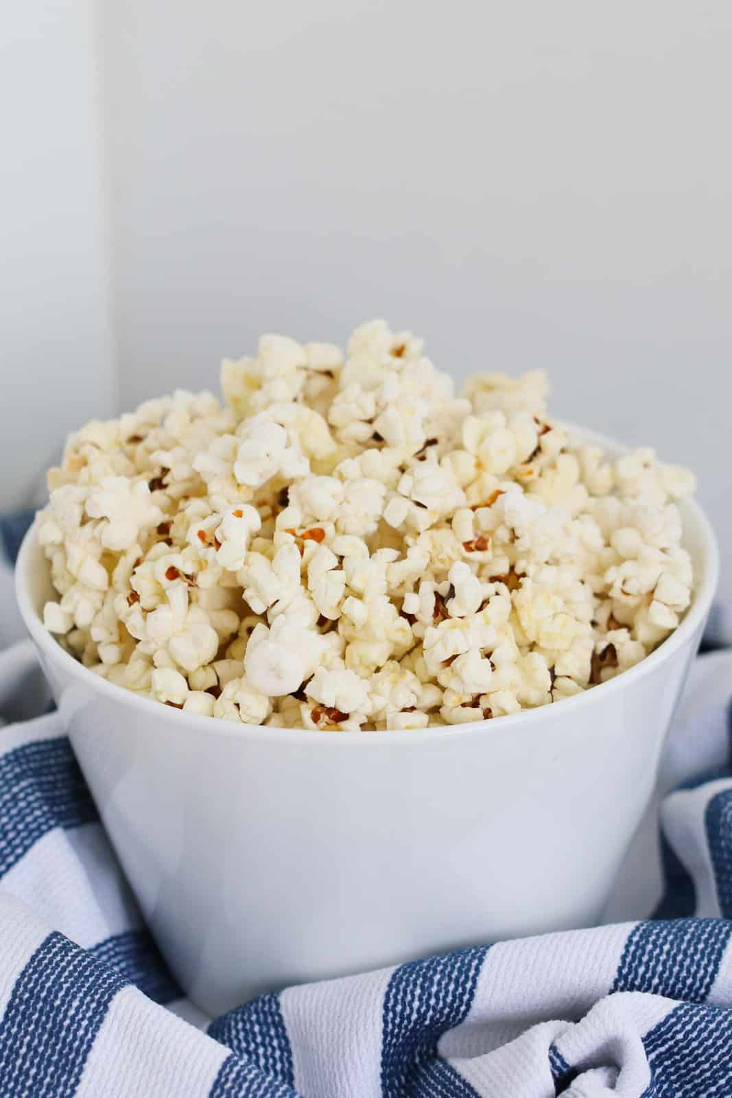 A white bowl of popcorn on a blue and white tea towel