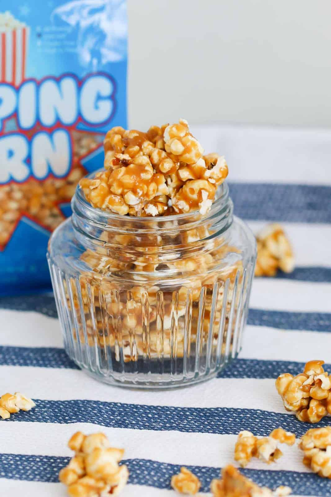A glass jar full of salted caramel popcorn on a striped tablecloth with a packet of popping corn in the background