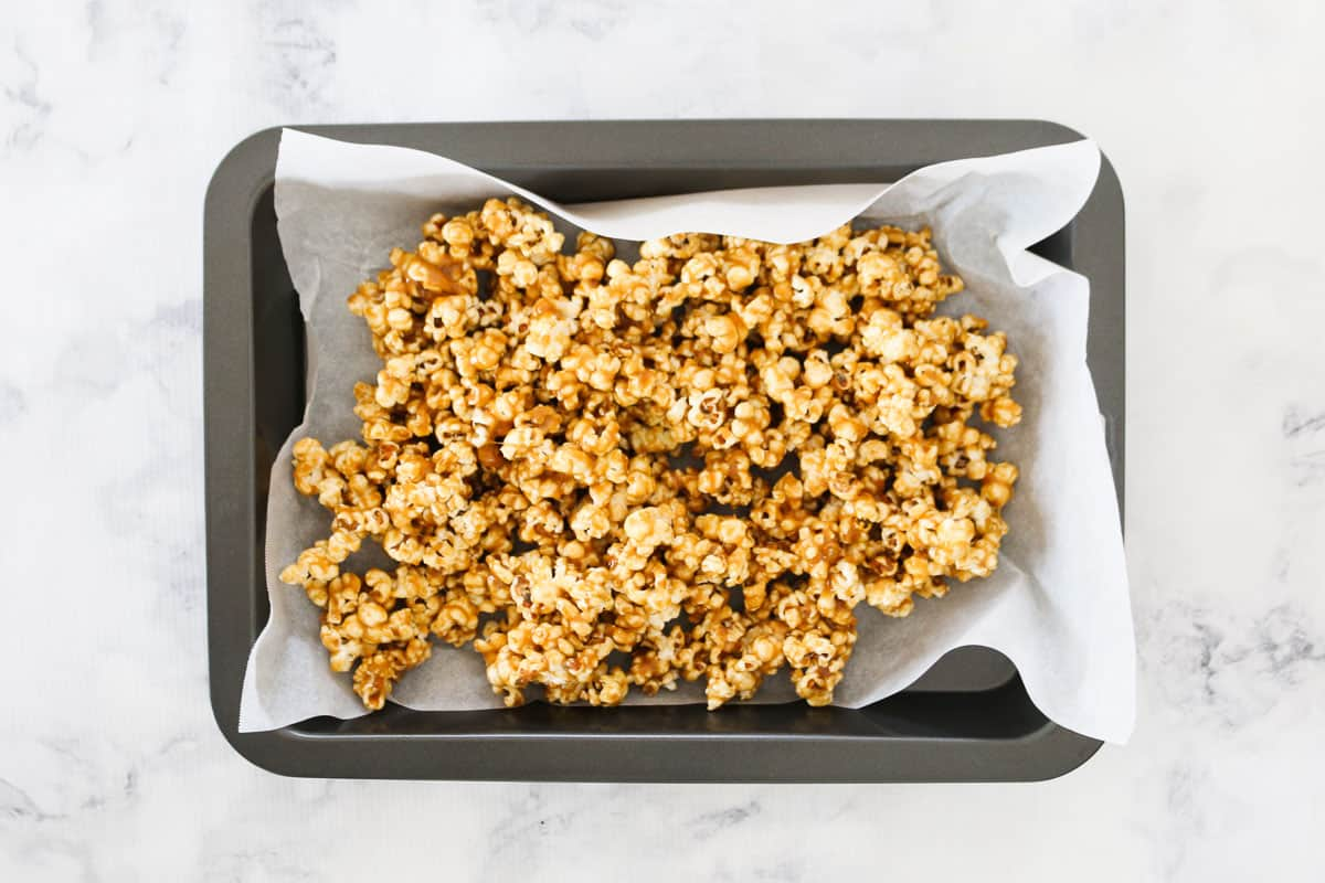 Caramel popcorn cooling on a paper-lined tray