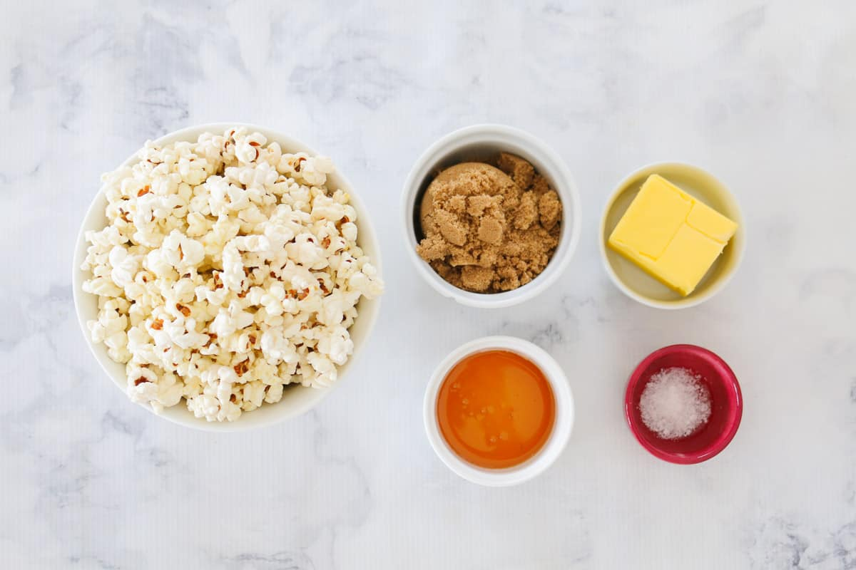 All the ingredients for salted caramel popcorn in individual bowls on a white marble bench