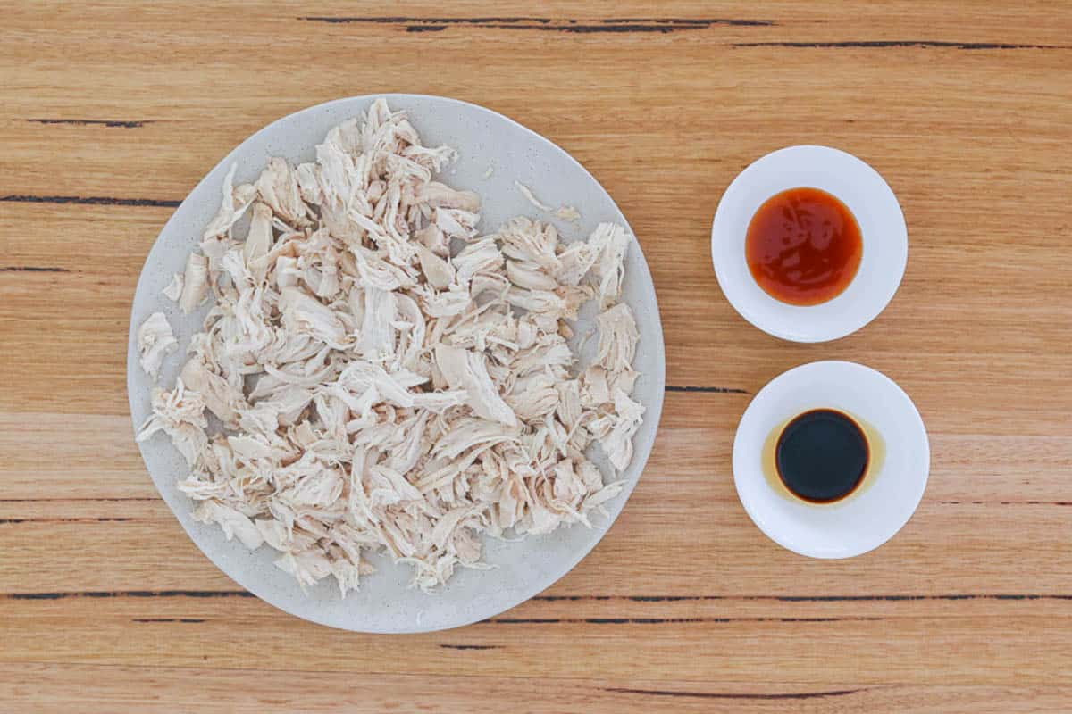 A plate of shredded chicken with small dishes of sweet chilli sauce and soy sauce next to it.