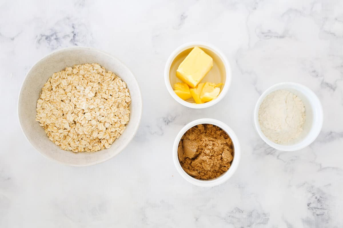 Ingredients for crumble in individual bowls on a marble bench