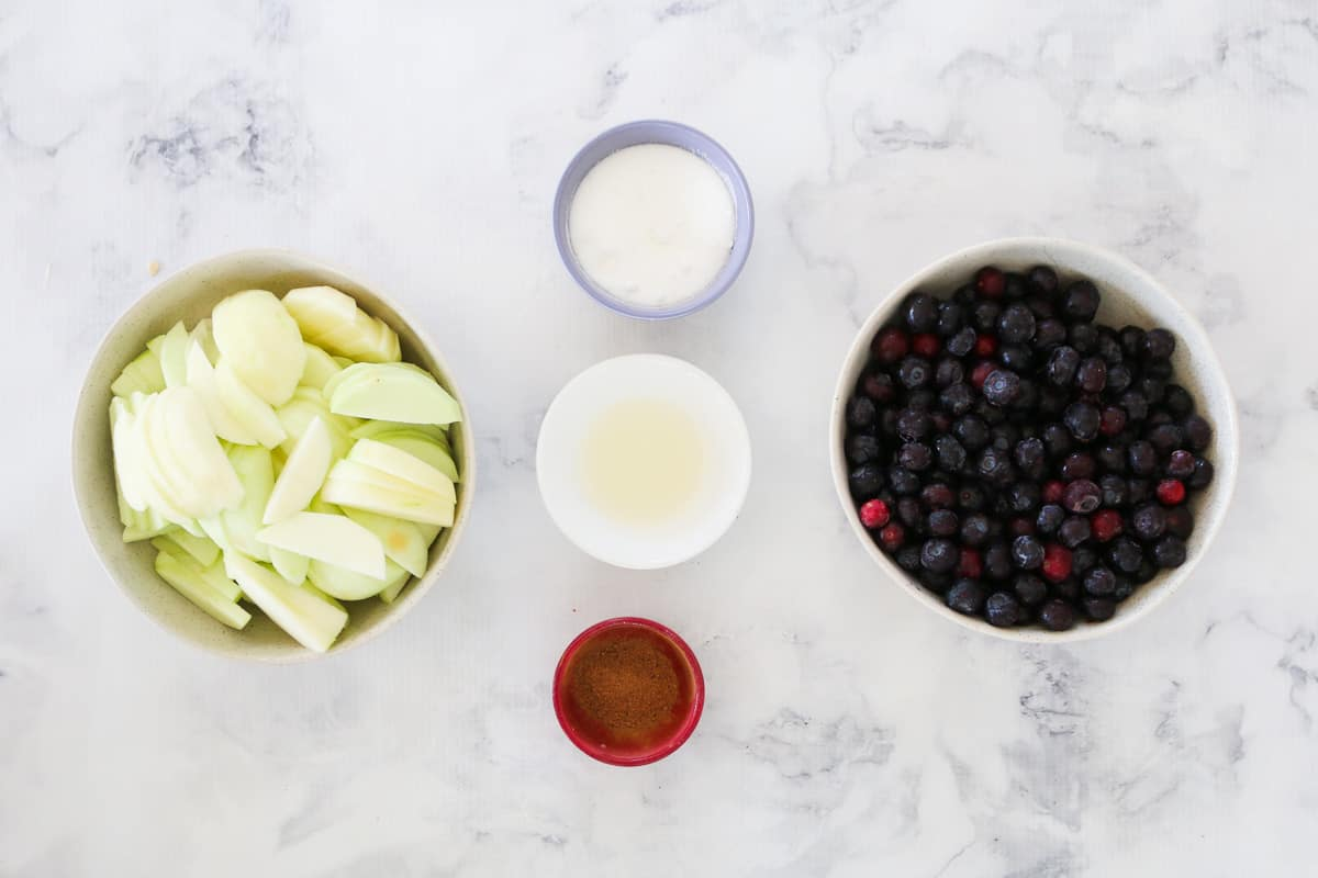 Apples, blueberries, sugar, water and spices in individual bowls on a marble bench