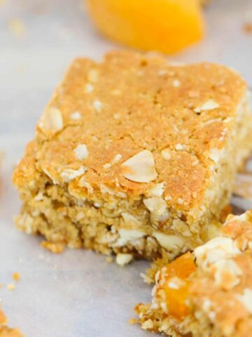 Pieces of oat slice with apricots on baking paper.