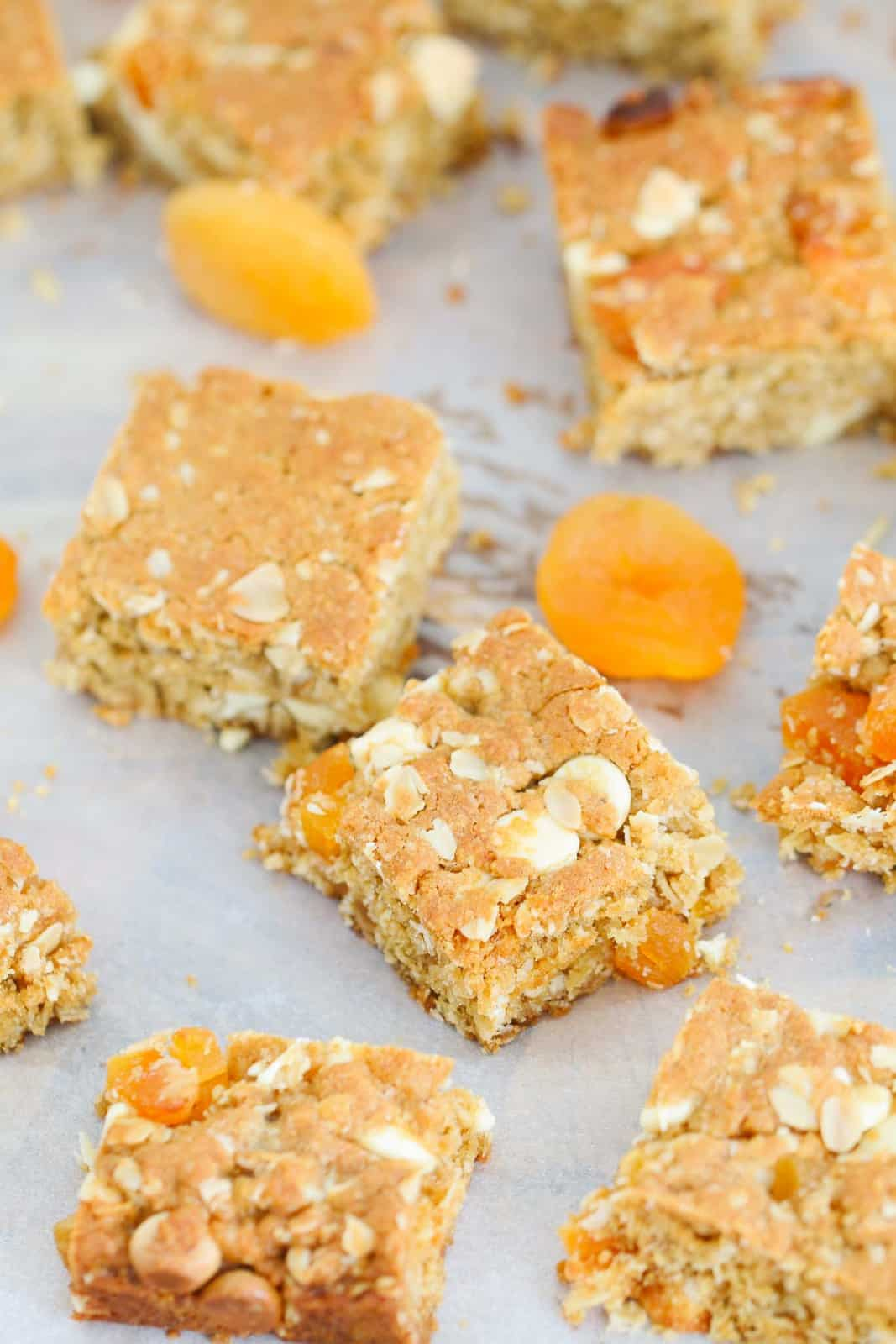 Apricot oat slice cut into squares with some dried apricots nearby