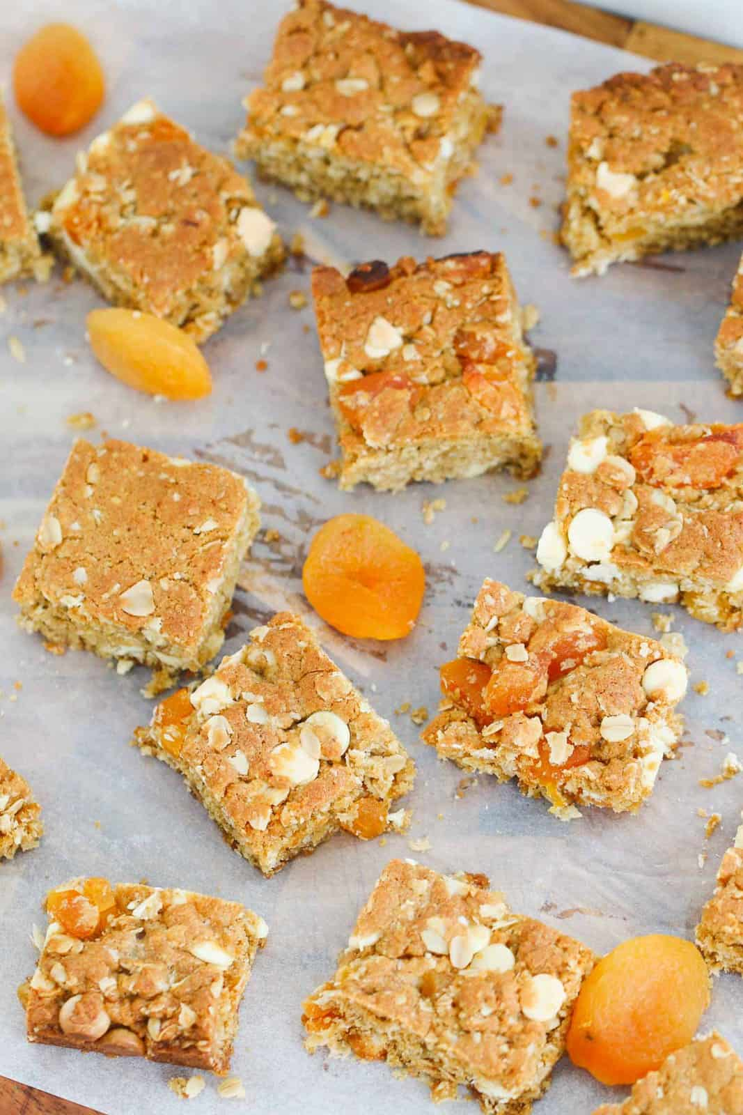 Pieces of apricot oat slice cut into squares on a piece of paper with dried apricots