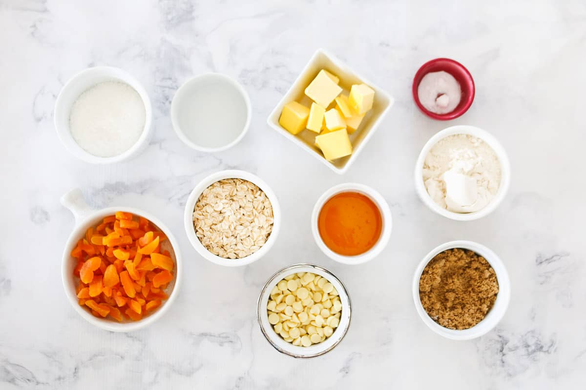 All the ingredients for apricot slice in individual white bowls on a white marble counter