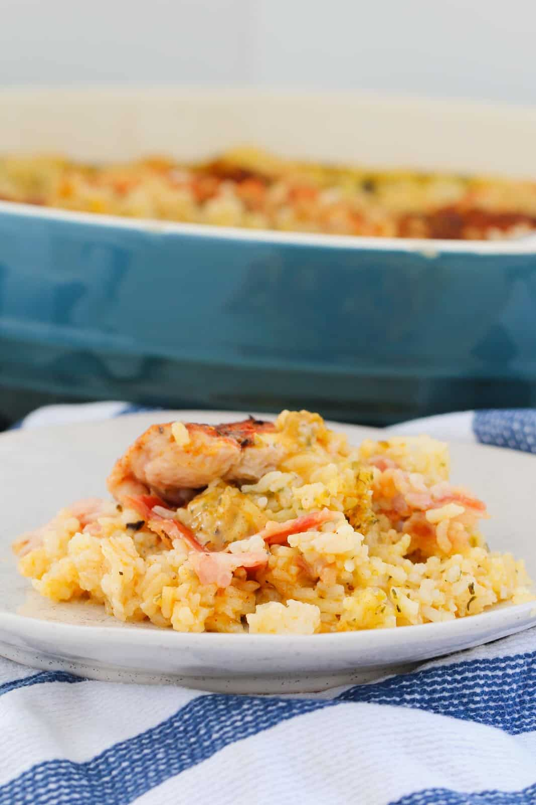 A serve of creamy chicken, bacon and rice casserole on a tea towel in front of a baking dish