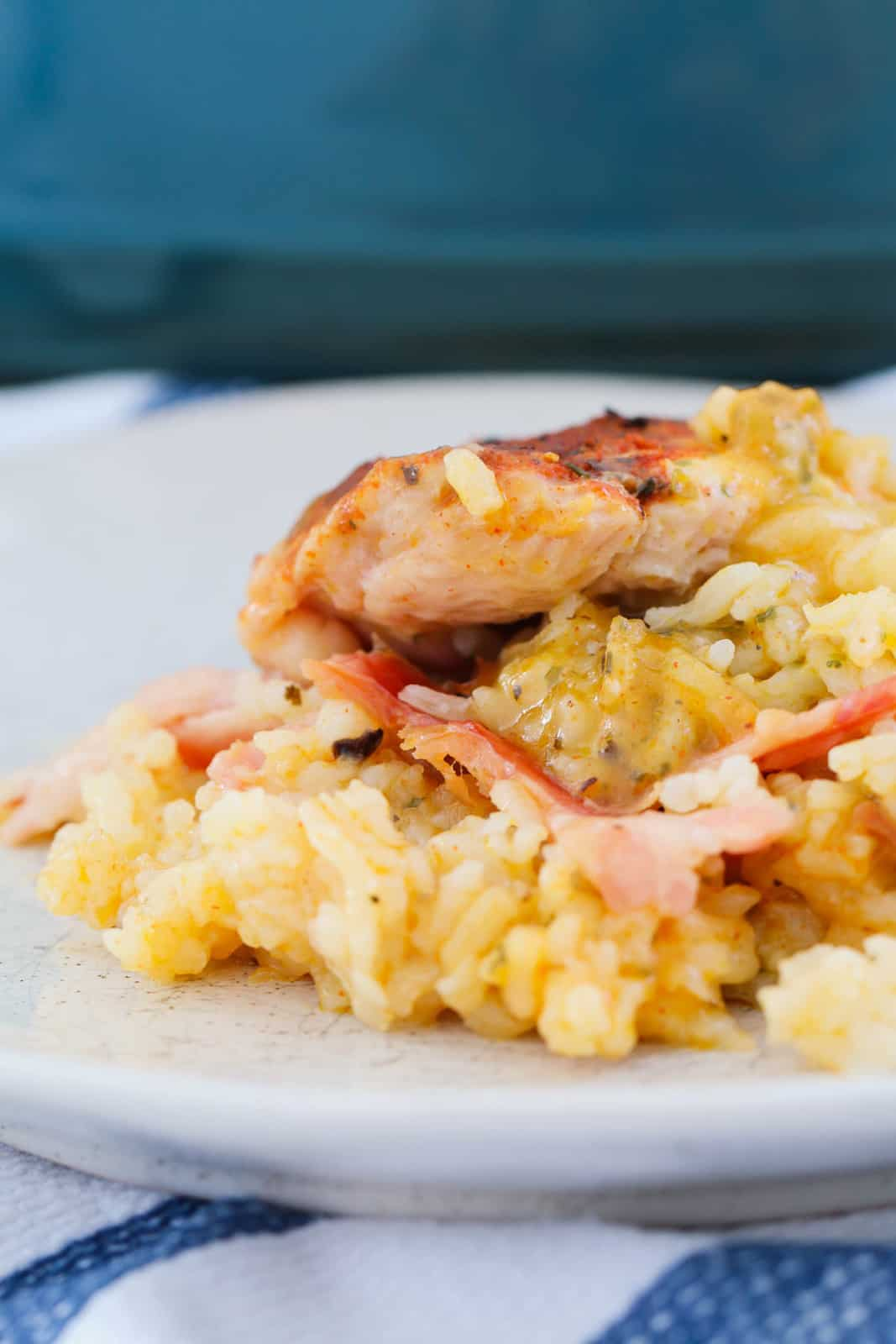 A white plate with a serve of creamy rice, bacon and chicken casserole