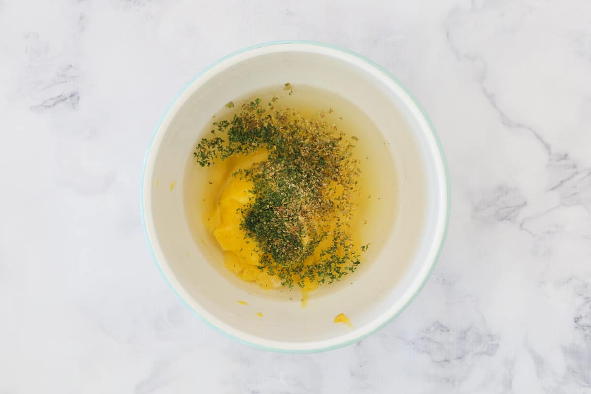 Cream of condensed chicken soup, water and herbs in a white bowl.