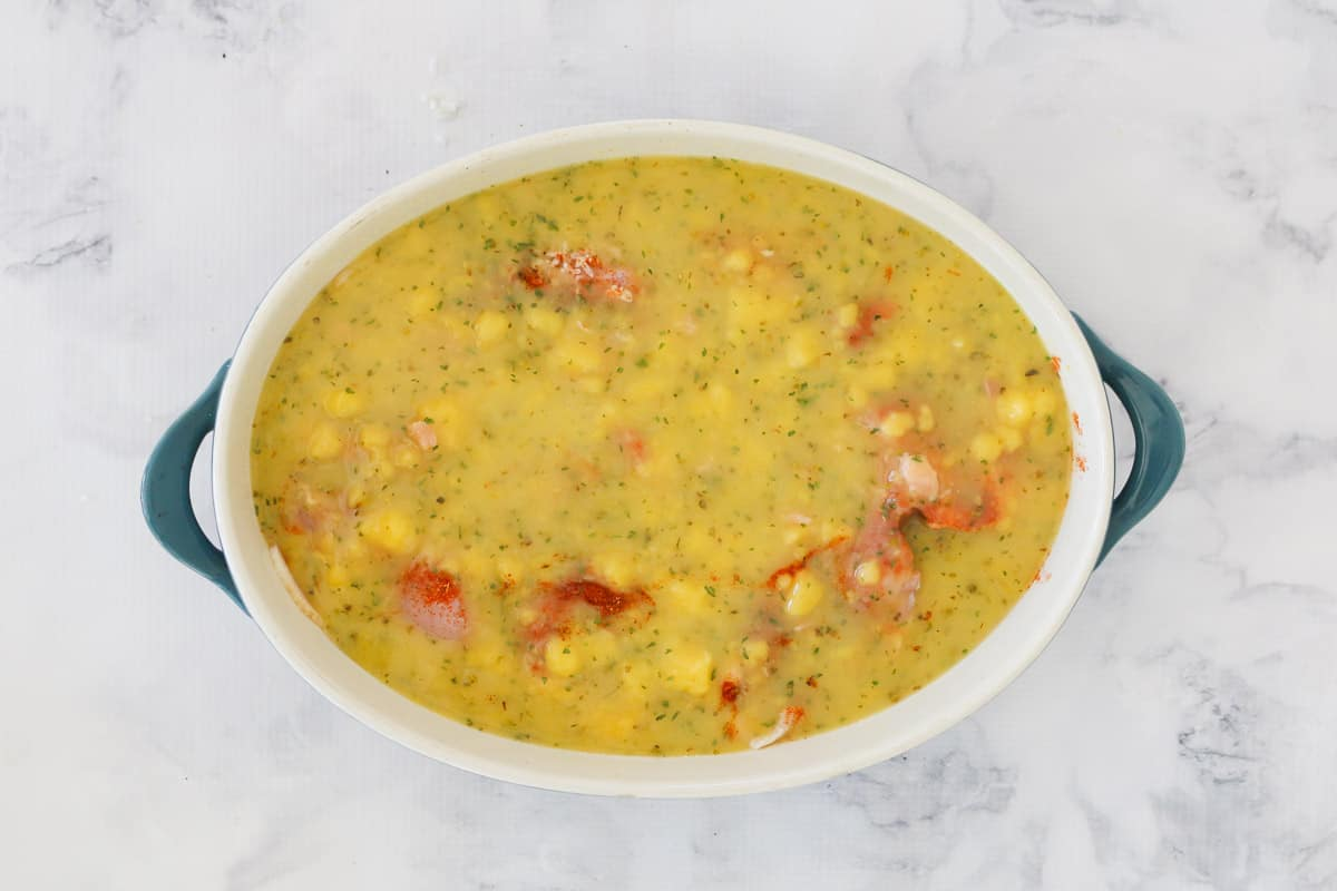 An oval baking dish filled with a creamy sauce over chicken, rice and bacon ready to be baked