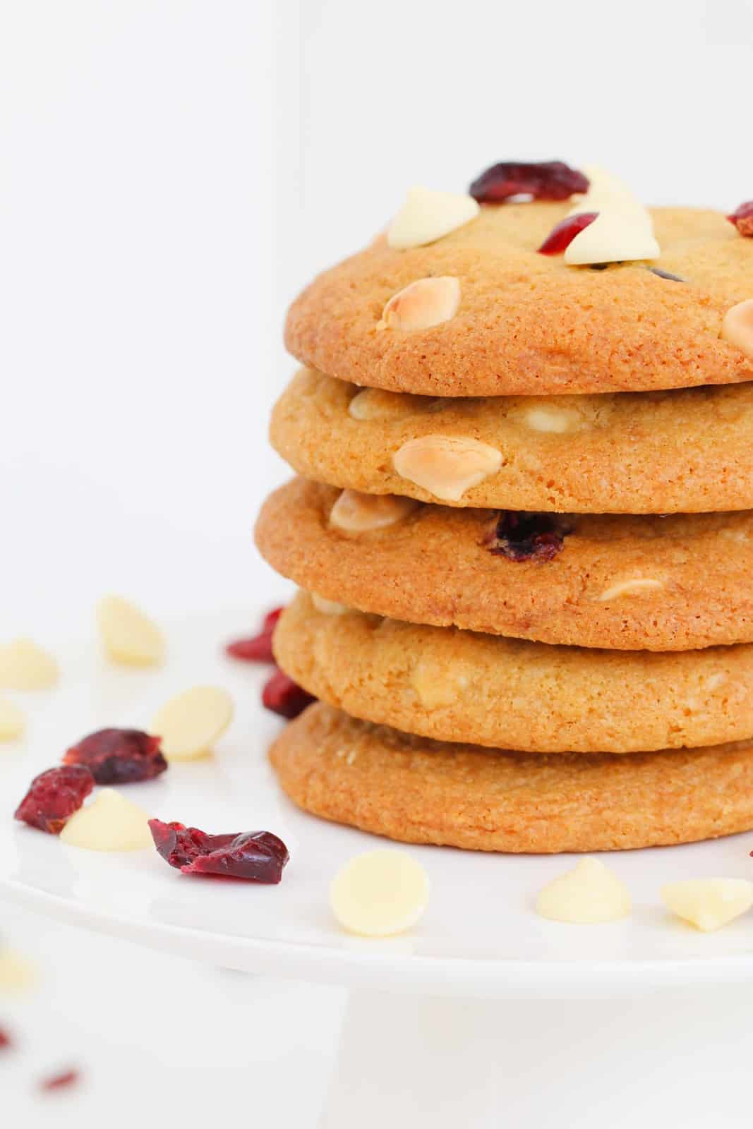 Five cookies stacked on a white cake stand surrounded by white chocolate chips and cranberries.