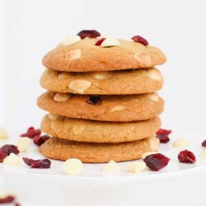A stack of cookies with white chocolate chips and cranberries.