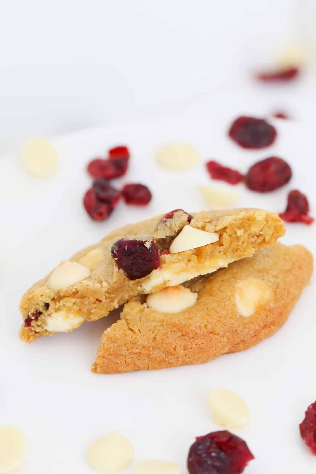 A cranberry cookie with white chocolate broken in half with a chewy soft inside on a white background.