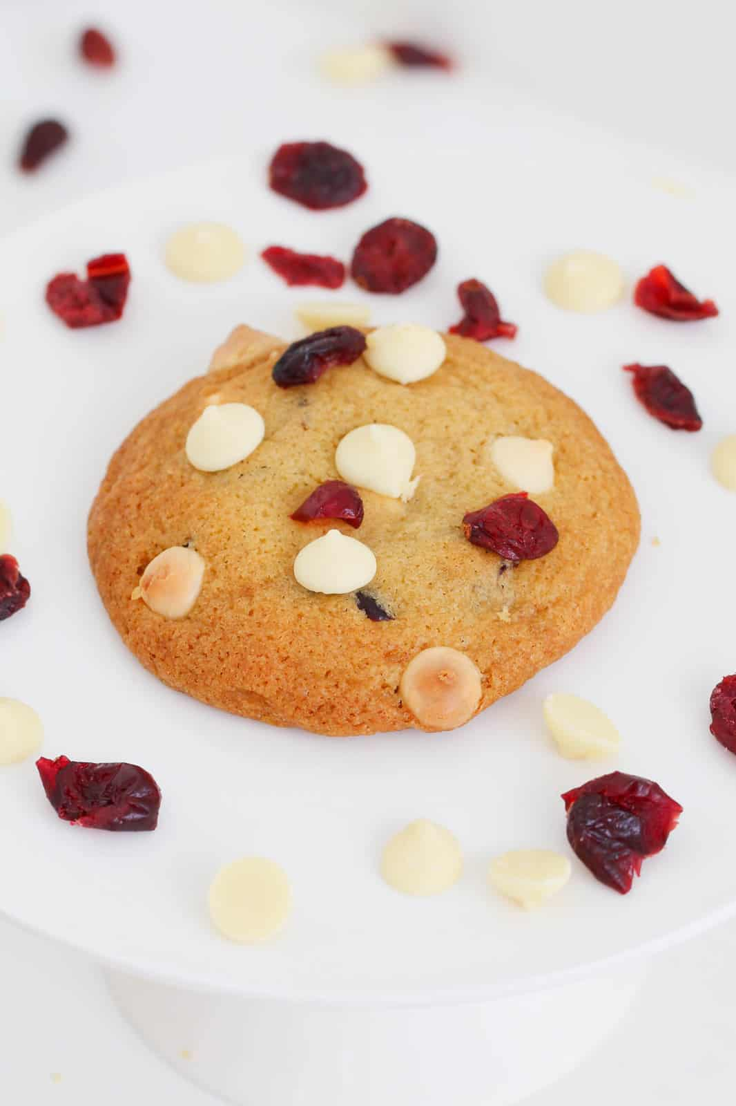 A cookie topped with white chocolate and cranberries, and more cranberries scattered around, on a white plate.