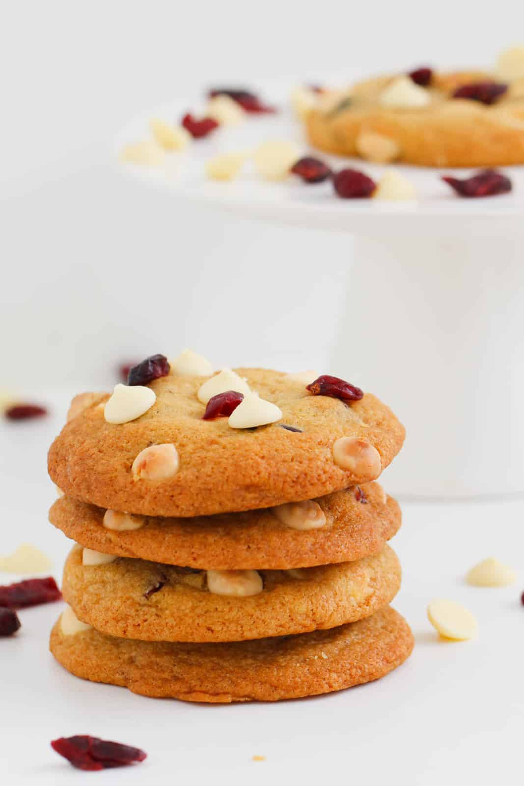 Four white chocolate and cranberry cookies stacked in a pile with white chocolate chips and dried cranberries scattered around
