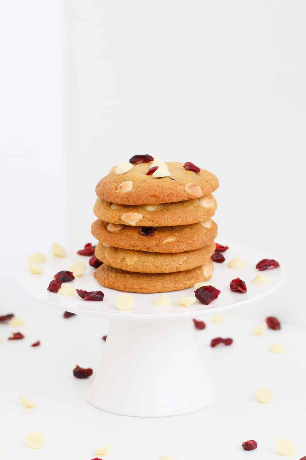 Five white chocolate and cranberry cookies stacked on a white cake stand with cranberries scattered around.