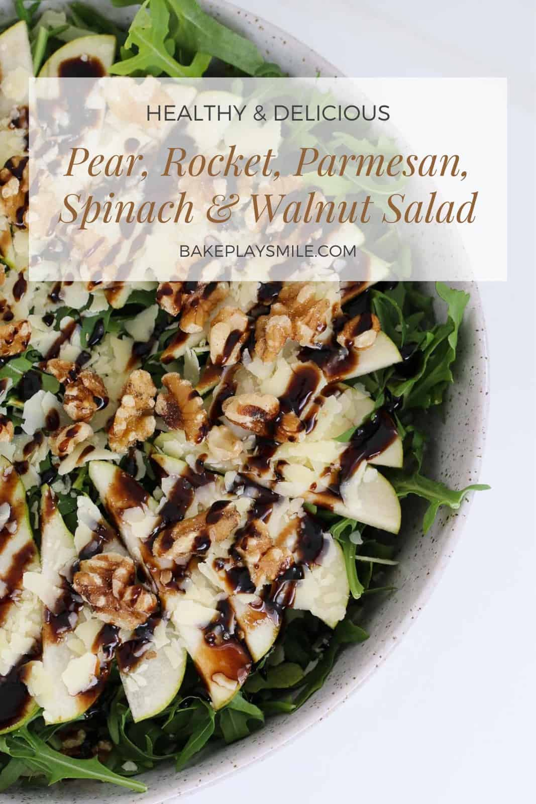 An overhead shot of a salad made with pear, rocket, walnuts and parmesan.