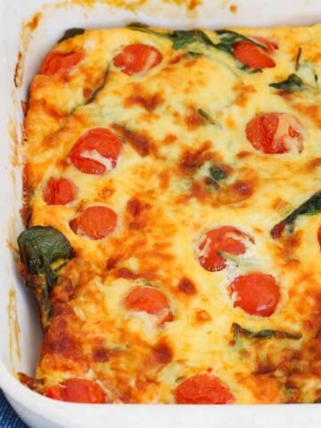 A white baking dish filled with an egg mixture, tomatoes, spinach and cheese.