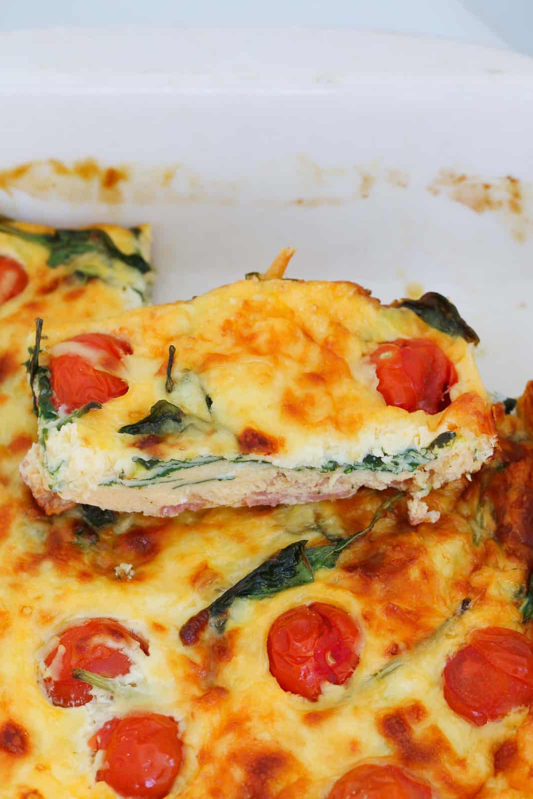 A close up of a piece of baked frittata with bacon, spinach and tomato.