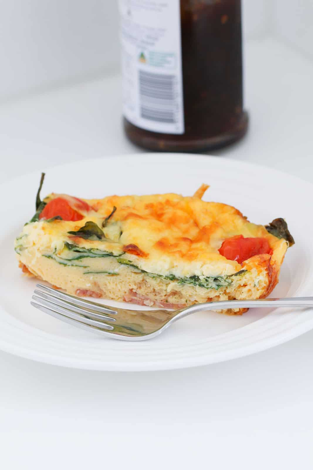 A piece of frittata on a plate with a fork in front.
