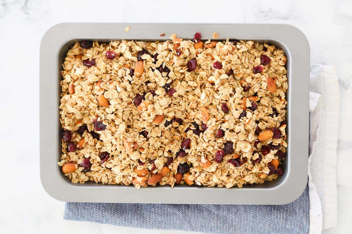 Granola in baking tray with dried cranberries mixed through